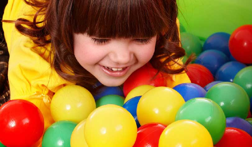 happy girl in a ball pit at play centre
