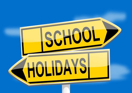 a road sign saying School Holidays